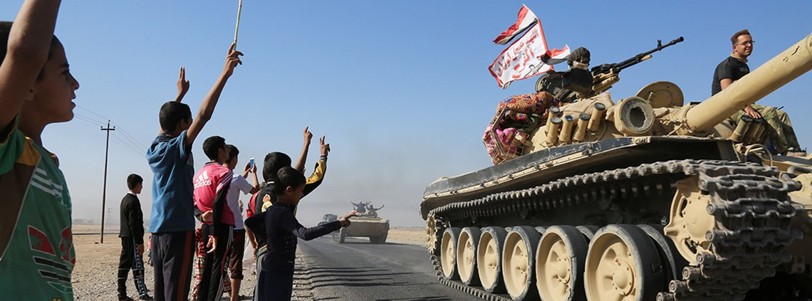 Civilians wave as Iraqi military forces pass through the city of Kirkuk. Not all of the city was happy with Kurdish control ©PA Images